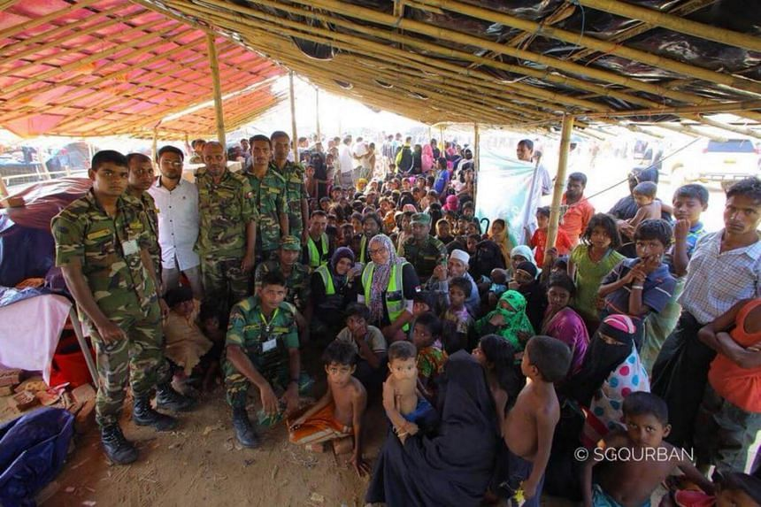 Mr Muhammad Firdaus (first man in neon vest from left) and his wife Ms Najihah Jofrie (first woman in neon vest from left) decided to go and help out at Rohingya refugee camps in Bangladesh for their fifth wedding anniversary and Mr Firdaus' 36th bir