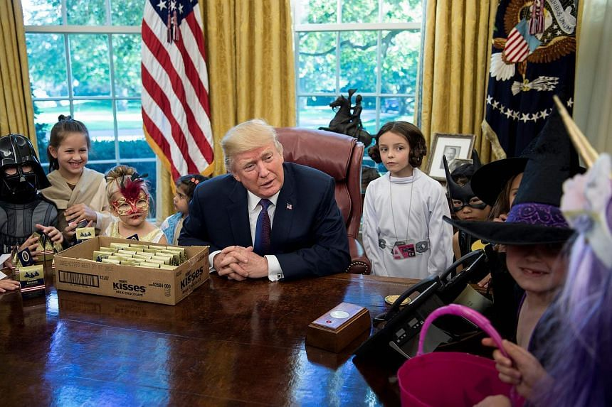 US President Donald Trump meets children of members of the press for Halloween in the Oval Office of the White House.