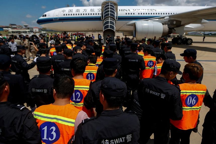 Chinese nationals (in orange vests) who were arrested over a suspected internet scam, are escorted by Chinese police officers before they were deported at Phnom Penh International Airport, in Phnom Penh, Cambodia, on Oct 12, 2017.