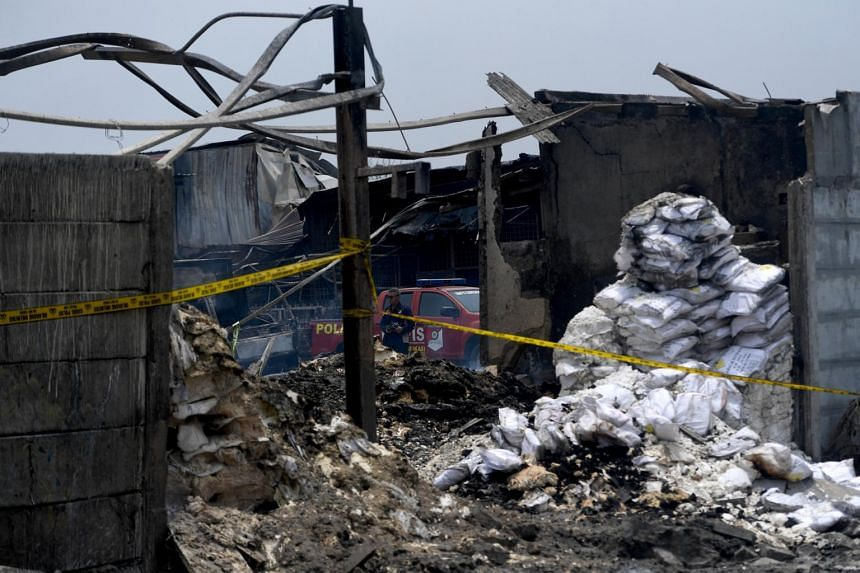 A police officer is seen at the site of the explosion at Kosambi village in Tangerang, Banten province, Indonesia.