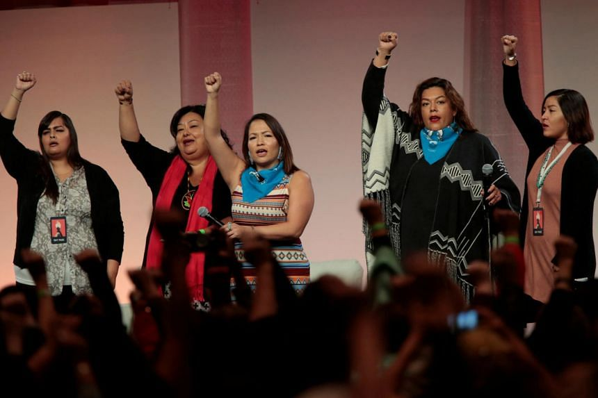 A group of Indigenous women raise their fists as they sing during the opening session of the three-day Women's Convention at Cobo Center in Detroit, Michigan, US.