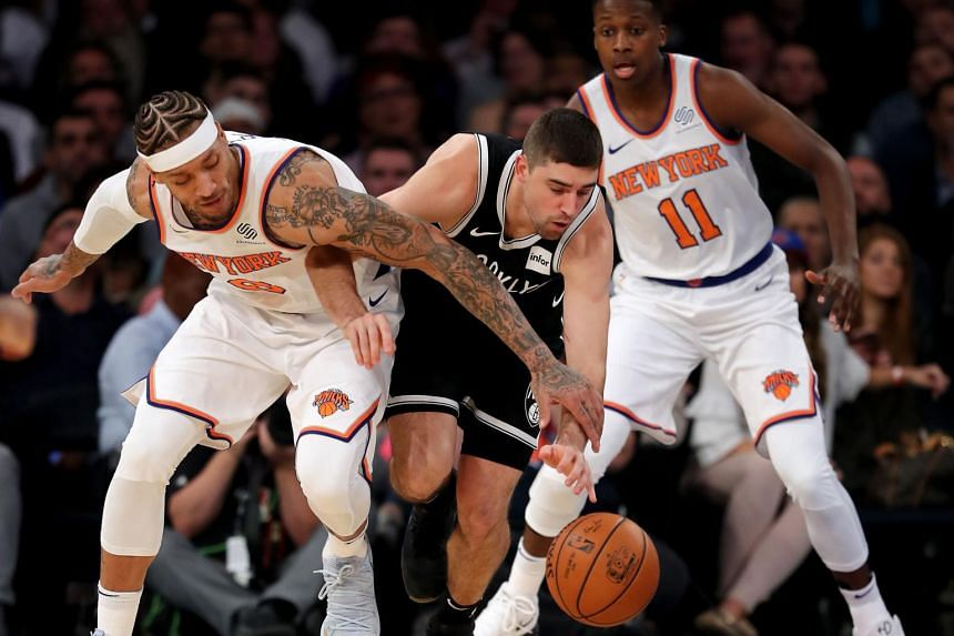 Michael Beasley #8 and Frank Ntilikina #11 of the New York Knicks fight for the ball with Joe Harris #12 of the Brooklyn Nets.