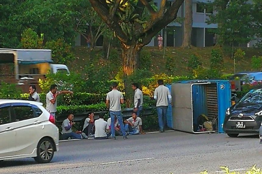 Five men are seen sitting on the side of the road along the Pan-Island Expressway while five others are standing around.