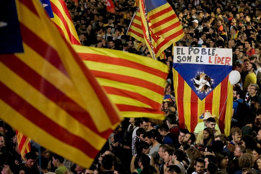 "A flag saying ""The people lead"" in Catalan is held up as people gather to celebrate the proclamation of a Catalan republic at the Sant Jaume square in Barcelona on Oct 27, 2017."