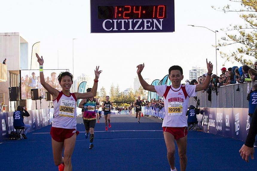 Singapore marathoner Jasmine Goh, accompanied by coach Lexxus Tan, crossing the finish line of the half-marathon at the Gold Coast Marathon in July. Researchers in Spain studied data gleaned from runners who participated in both distances at the Madr