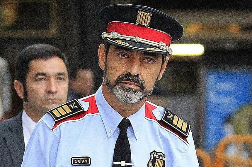 """Mr Josep Lluis Trapero, the highest-ranking officer of the Mossos d'Esquadra regional police. Sacked Catalan president Carles Puigdemont and his wife Marcela Topor during a walkabout yesterday. Mr Puigdemont said he and his team would keep working """"t"""
