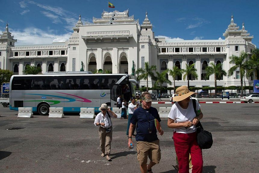 Tourists walking in front of the City Hall in downtown Yangon on Oct 12, 2017.