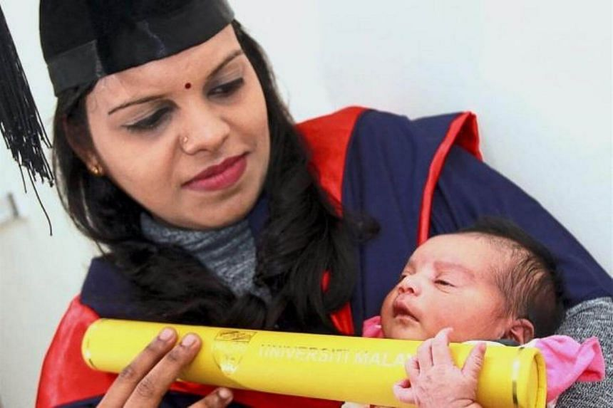 Dr Saritha holding her degree with her newborn baby at home in Nilai.