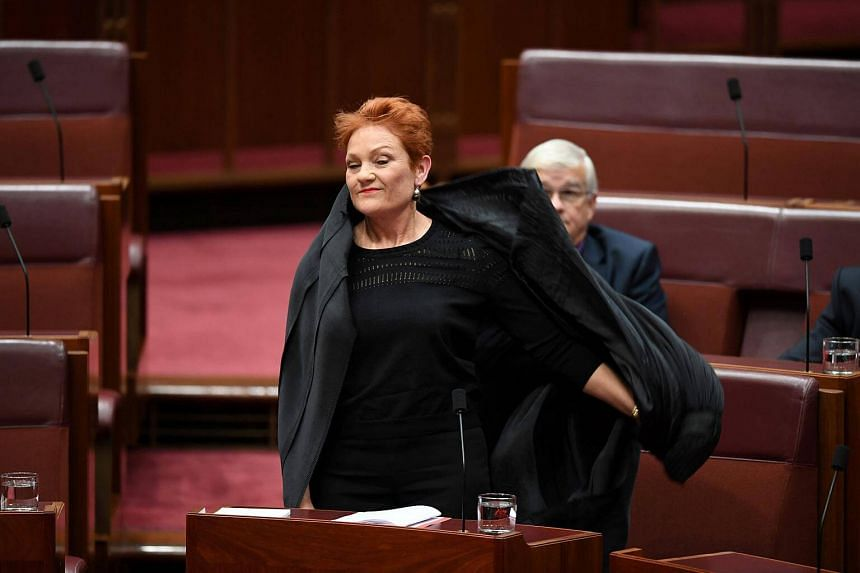 Australian One Nation party leader Senator Pauline Hanson pulls off an Islamic veil in the Senate chamber at Parliament House in Canberra, Australia.