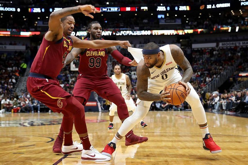 DeMarcus Cousins #0 of the New Orleans Pelicans is fouled by Jae Crowder #99 and Channing Frye #8 of the Cleveland Cavaliers.