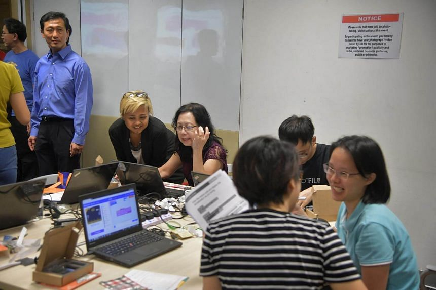 Education Minister Ong Ye Kung watches as retiree, Wong L.P. (third from left) assisted by Teaching assistant, Carmen Luz, (second from left) at a robotics workshop organised by Roboto Academy at the Lifelong Learning Festival 2017.