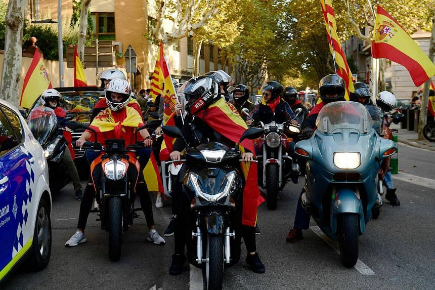 Some people on bikes ride wrapped in Spanish and Catalan flags during a demonstration calling for unity in Barcelona.