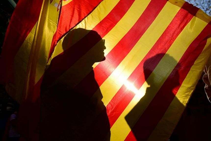 Protesters demonstrating with Spanish and Catalan flags during a march calling for unity, in Barcelona on Oct 29, 2017.