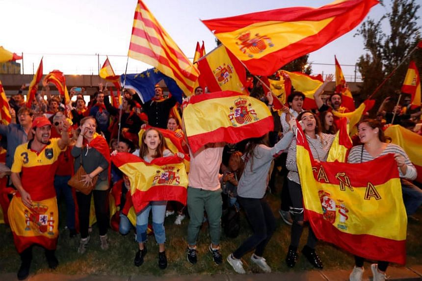 Pro-unity protesters waving Spanish and Catalan flags during a demonstration in Barcelona on Oct 28, 2017.