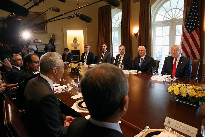 PM Lee Hsien Loong (third from left, back facing camera) and members of the Singapore delegation speaking with US President Donald Trump and US officials during a working lunch at the White House on Oct 23, 2017.