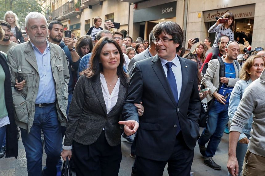 """Sacked Catalan president Carles Puigdemont and his wife Marcela Topor during a walkabout yesterday. Mr Puigdemont said he and his team would keep working """"to build a free country""""."""