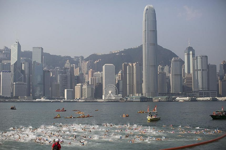 Participants in the New World Harbour Race crossing the starting line at the Tsim Sha Tsui waterfront in Hong Kong yesterday. Around 3,000 swimmers took part in the 1km race across Victoria Harbour from Tsim Sha Tsui, on the Kowloon side, to Wan Chai
