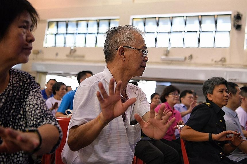 Stroke survivor Lim Huah Yong (centre) and his wife taking part in a mass exercise at Hong Kah North Community Club yesterday.