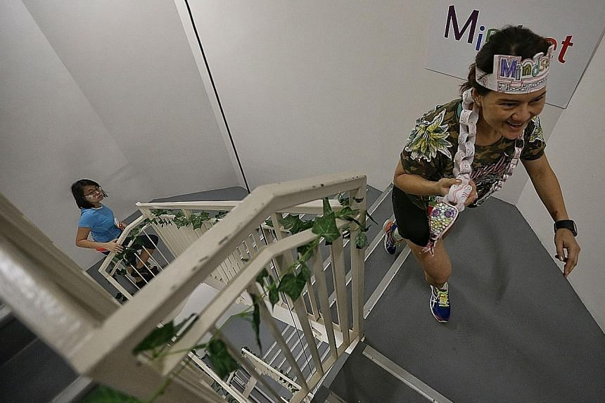 Ms Dora Chua, a receptionist with Jardine Cycle and Carriage, dressed in her jungle-themed outfit, climbing the 33 floors of Marina Bay Financial Centre Tower 1, during the Mindset Challenge and Carnival.