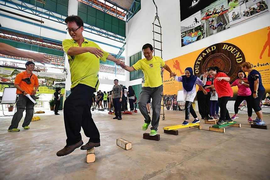 Parents celebrate after completing a task in which everyone has to pass a ball to the next person at the same time without dropping any of the balls. Engineer Derick Choo, 46, and other parents work together, using planks and blocks to move from one