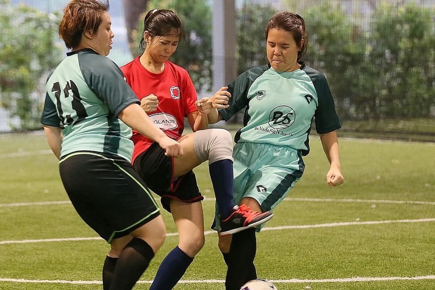 From left in green: Touch Silent Strikers C's Tina Li and Lim Jia Yi tackling Ninja Turtles' Neoh Yew Kim (in red) in the women's futsal final at the third National Deaf Games yesterday. Touch won 2-0. The futsal tournament marked the first of four s