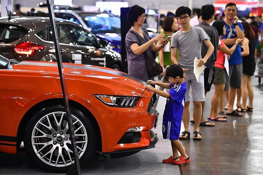 Five-year-old Jayden Goh checking out a Ford Mustang convertible at the Cars@Expo yesterday. Held over the weekend and organised by ST Classifieds, Singapore Press Holdings' automobile retail bazaar attracted more than 130,000 visitors and saw some 4