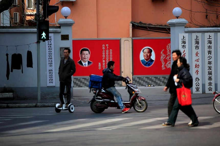 People cross a street in front of posters depicting late Chairman Mao Zedong (right) and China's President Xi Jinping in Shanghai.
