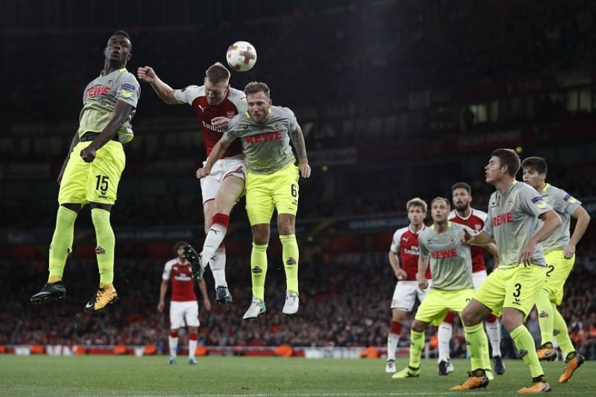 Arsenal's German defender Per Mertesacker (2nd left) vies with FC Cologne's Colombian striker Jhon Andres Cordoba Copete (left) and FC Cologne's German midfielder Marco Hoger during the UEFA Europa League Group H football match between Arsenal and FC