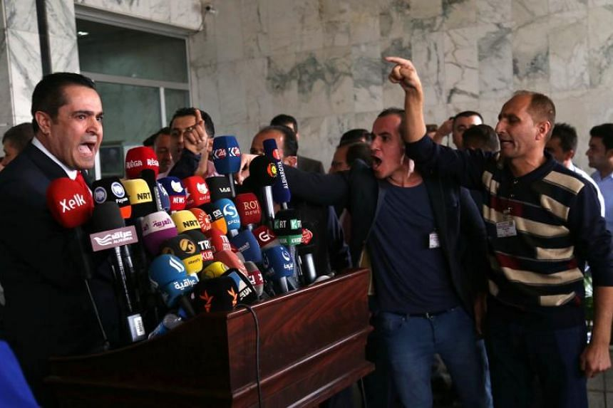 Iraqi Kurdish men protest as Rabon Maarouf, an independent member of Kurdistan's parliament, gives a press conference outside the parliament, in Arbil, the capital of Iraq's autonomous northern Kurdish region, on Oct 29, 2017.