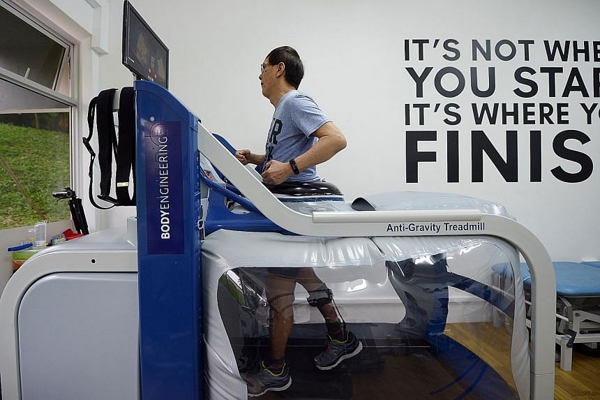 """A patient goes through his physical training at the Stroke Support Station on the AlterG, a machine that """"reduces"""" body weight by up to 80 per cent to allow patients to strengthen their muscles gradually without putting excessive weight on their stro"""