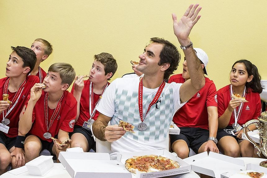Roger Federer sharing pizza with ball kids after defeating Juan Martin del Potro to take the Basel Open for the eighth time. His withdrawal from this week's Paris Masters means Rafael Nadal should finish the year as world No. 1 for the fourth time.