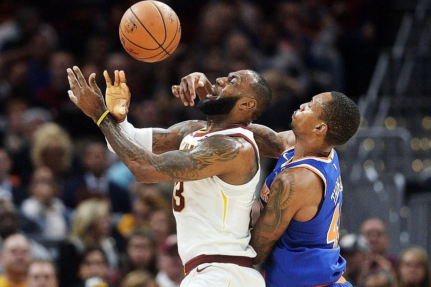 Knicks forward Lance Thomas fouling Cavaliers forward LeBron James at Quicken Loans Arena in Cleveland. New York won the game 114-95.