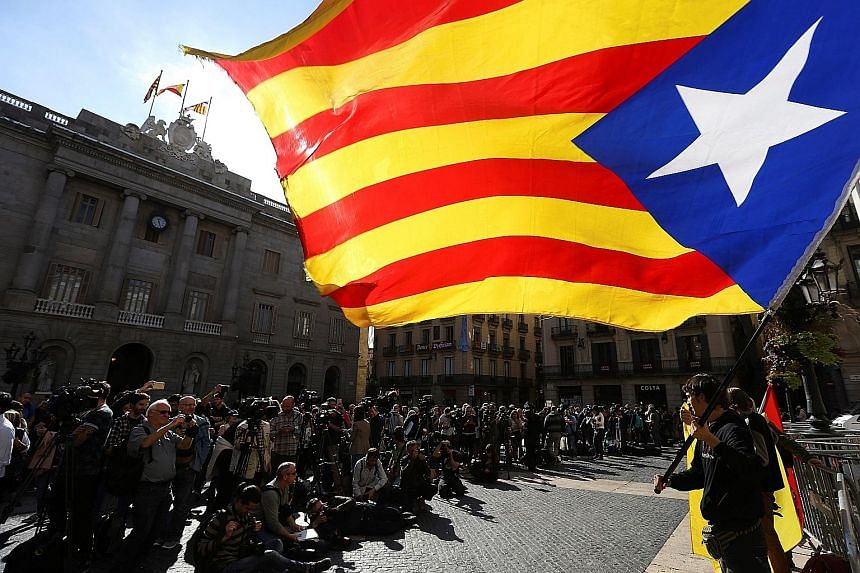 A demonstrator waving a Catalan flag outside the region's Palau de la Generalitat in Barcelona yesterday. The main civic groups behind the pro-independence campaign had called for widespread civil disobedience but most workers started their working d