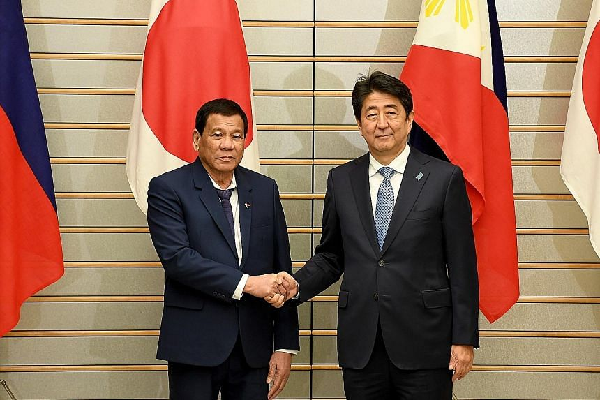 Philippine President Rodrigo Duterte meeting Japanese Prime Minister Shinzo Abe before talks at Mr Abe's official residence in Tokyo yesterday. The two leaders discussed issues, including how to deal with North Korea.