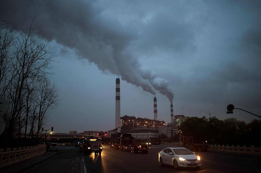 A file photo of cars passing the Shanghai Waigaoqiao Power Generator Company coal power plant in Shanghai, on March 22, 2016.