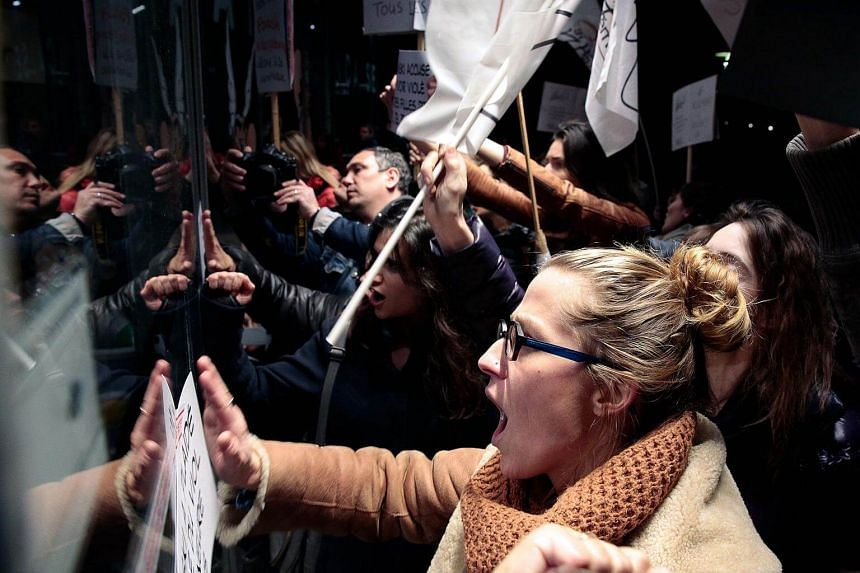 Protesters hit on a window during a demonstration outside the Cinematheque Francaise film archive in Paris that film-maker Roman Polanski attended.