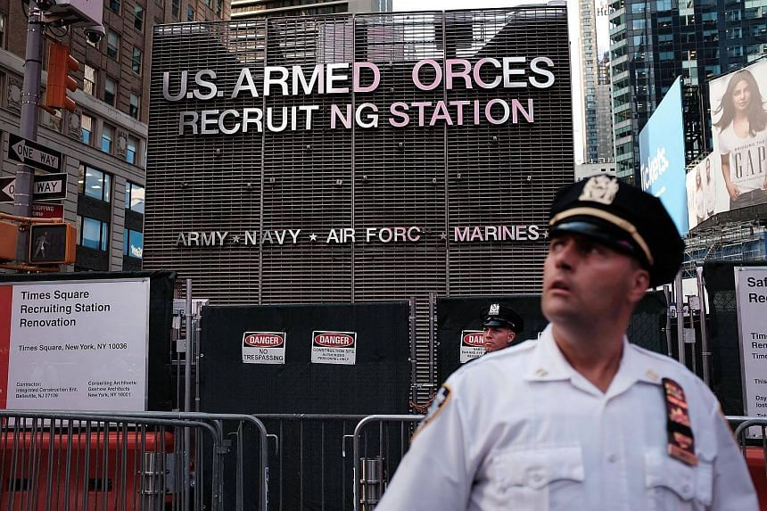 A police officer standing guard as dozens of protesters gather in Times Square near a military recruitment center to show their anger at President Donald Trump's decision to reinstate a ban on transgender individuals from serving in the military in N