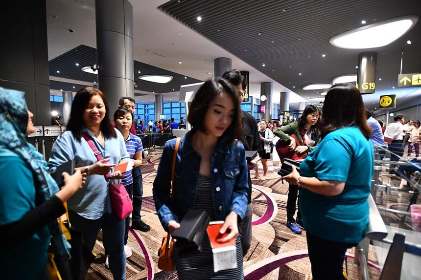 Passengers from first flight Cathay CX650 getting a free luggage tag from Cathay before boarding the plane.