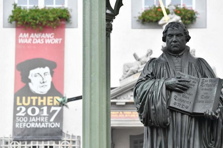 A statue of German Church reformer Martin Luther holding a book including his translation into German of the New Testament of the Bible is pictured in Wittenberg, eastern Germany on Oct 31, 2017.