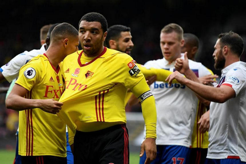 Watford's Troy Deeney is pulled away by Richarlison during the Premier League in Watford, Britain, on Oct 28, 2017.