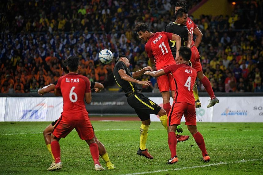 """Singapore's Ikhsan Fandi heading the ball during the SEA Games football match against Malaysian on Aug 16, 2017. Malaysia's football association was fined US$30,000 after fans called Bruneians and Singaporeans """"dogs"""" during their football matches."""