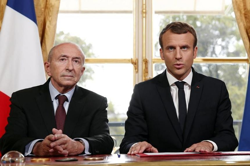 French President Emmanuel Macron (right) addresses the press, flanked by French Interior Minister Gerard Collomb (left) and French Prime Minister Edouard Philippe (unseen) after he signed a counterterrorism law at the Elysee Palace in Paris, France,
