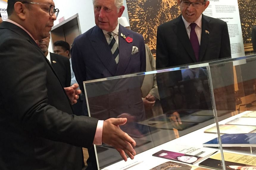 Britain's Prince Charles looks at books on interfaith efforts while on a tour of the Harmony Centre in Bishan.
