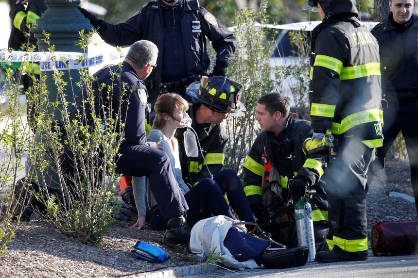 A woman is aided by first responders after sustaining injury on a bike path in Lower Manhattan.