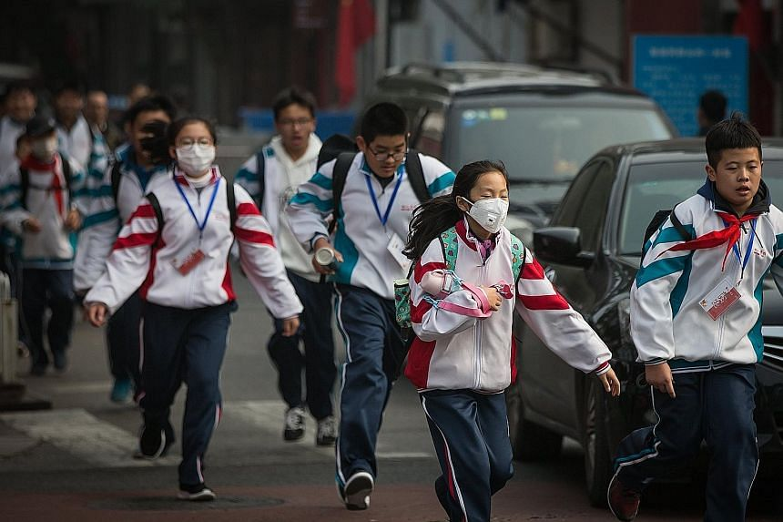Some students wearing masks as protection against the polluted air last Friday in Beijing, China. As the world's top emitter of greenhouse gases, China has said it aims to bring an overall decline in carbon emissions from 2030. A national cap-and-tra