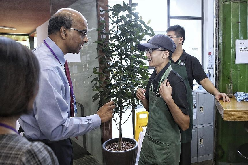Deputy Prime Minister Tharman Shanmugaratnam with barista Salihin Nakmin, 21, at the Art+Coffee cafe, part of The Art Faculty by Pathlight at the Enabling Village, yesterday. Mr Tharman was attending the launch of a book to mark the 20th anniversary