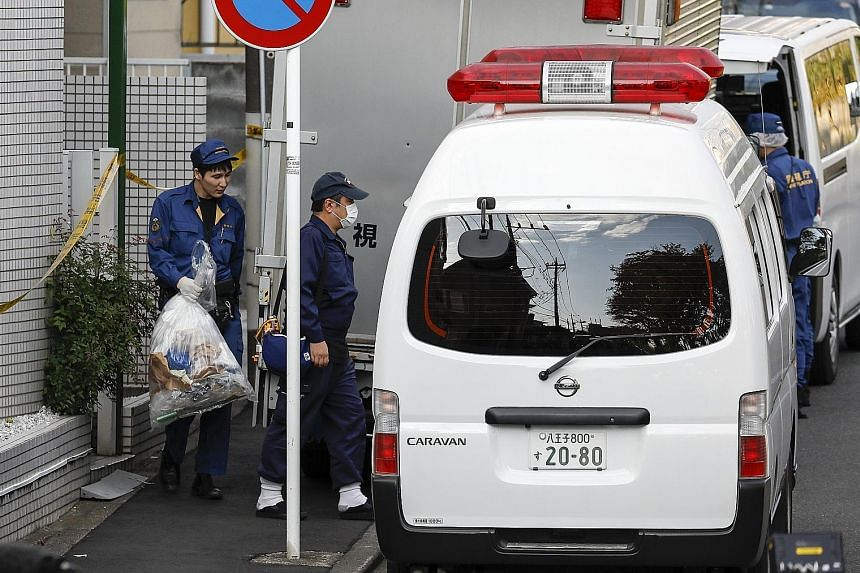 Above: The two-storey apartment (with blue sheet) in Zama city in Kanagawa prefecture, Japan, where the body parts were found. Left: Investigators removing items from the flat yesterday. Home owner Takahiro Shiraishi told police he cut up his victims