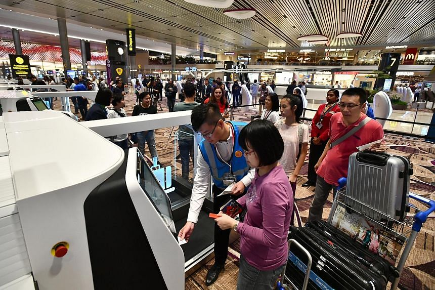 Passengers from Cathay Pacific CX650, the inaugural flight to depart from Terminal 4, using the automated bag drop yesterday. Passengers from Cathay Pacific CX659 from Hong Kong, the first flight to arrive at Terminal 4, were greeted by airport staff