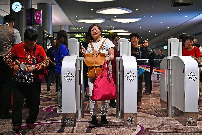 Hong Kong-bound passengers on their way to board Cathay Pacific Flight CX650, the first flight to depart Changi Airport's Terminal 4 yesterday. They were the first to experience the new terminal's automated do-it-yourself processes for check-in, bag