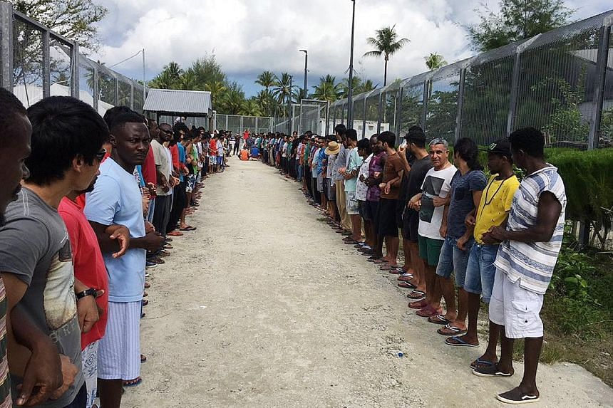 Refugees linking hands in solidarity ahead of the closure of the Manus Island detention centre in Papua New Guinea yesterday. Canberra has insisted that the detainees are not welcome in Australia.
